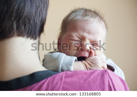 Cute newborn girl crying in the arms of mother - stock photo