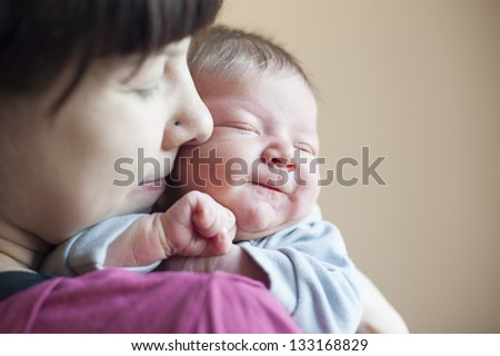 Cute newborn girl in the arms of mother smile - stock photo