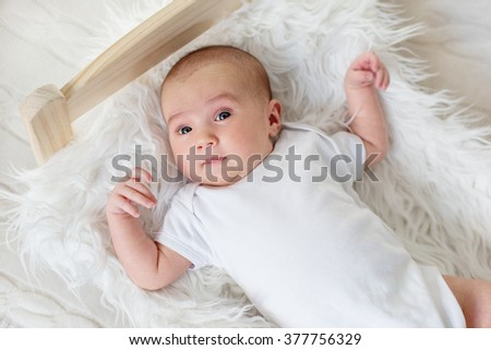 cute newborn girl lying in bed on a white background