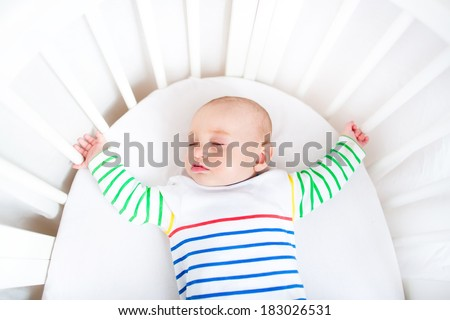 Cute newborn little boy sleeping in a white round crib - stock photo