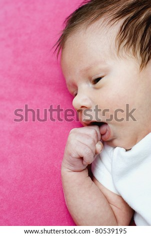 Cute newborn sleeping with finger in mouth on red blanket - stock photo