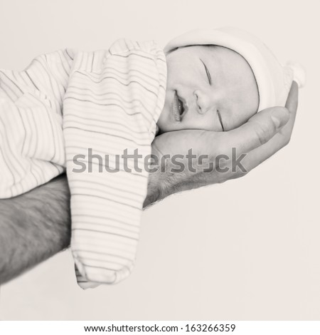 Cute newborn sleeps and smiles at her father's hand on a white background (black and white) - stock photo
