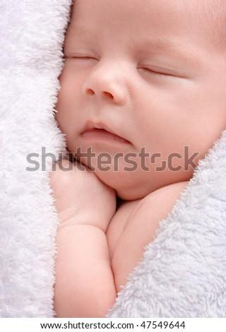Cute newborn sleeps wrapped in white blanket, shallow DOF - stock photo