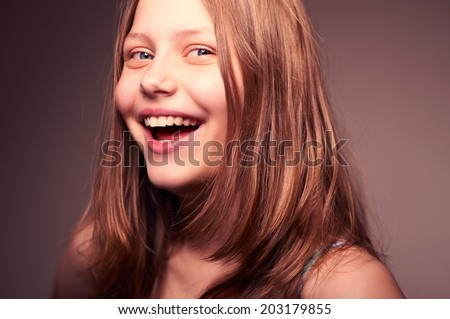 Cute nice happy teen girl looking at the camera and laughing