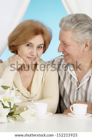 Cute old couple at table on blue in the morning - stock photo