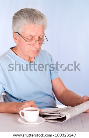 cute old man reading newspaper at table