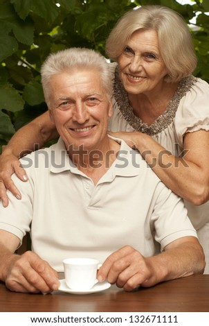 Cute older couple sitting at a table at home on the veranda - stock photo