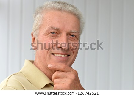 cute older man poses in a room