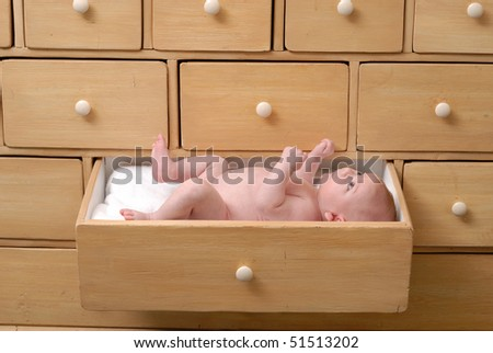 cute one month baby lying in a drawer of an old beige cabinet with white buttons