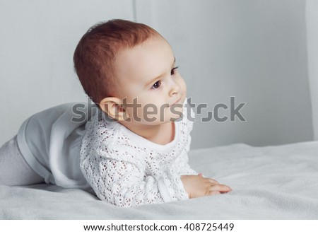 cute one year old baby in bed at home - stock photo