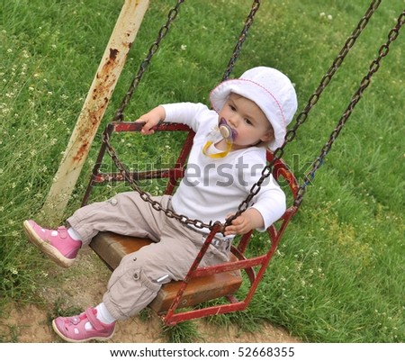 cute one year old girl having fun on a swing