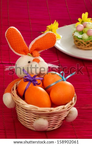 Cute orange bunny - basket with easter eggs on red mat - stock photo