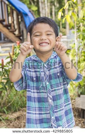Cute outdoor portrait of happy smiling Asian Thai little boy - stock photo