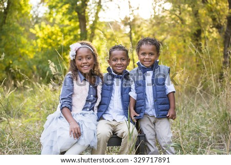 Cute outdoor portrait of three racially diverse children - stock photo