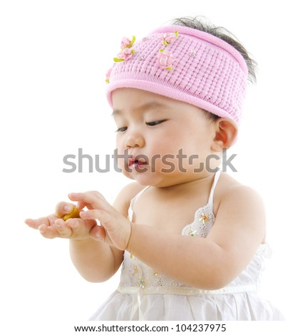 Cute pan Asian baby girl eating on white background - stock photo