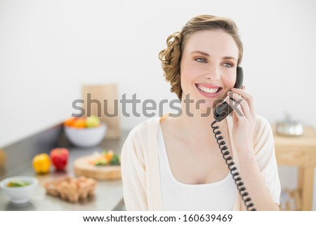 Cute peaceful woman phoning with a telephone in her kitchen at home - stock photo