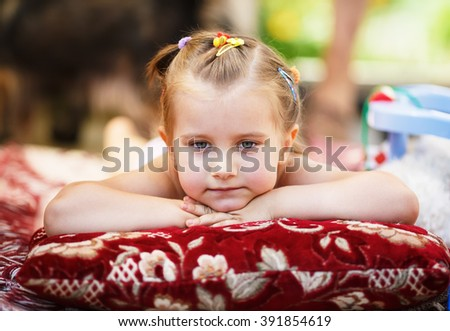 Cute pensive child lying on a blanket in the park. Close-up of baby girl resting her head on her hands. Shallow depth of field. Selective focus. - stock photo