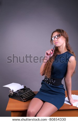 Cute pensive female author with vintage typewriter - stock photo