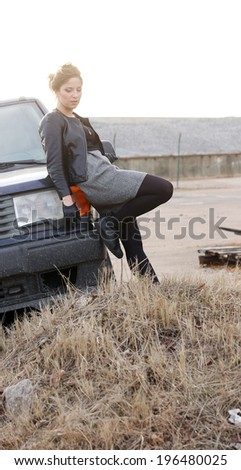 Cute, pensive girl by the car