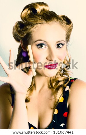 Cute Pin-up Housewife Holding Old Fashioned Wooden Laundry Peg When Cleaning In Stylish Polkadot Fashion - stock photo