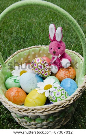 Cute pink toy bunny in basket of colorful Easter eggs with daisies on grass background