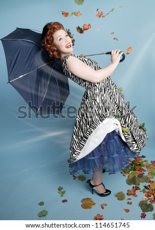 Cute pinup girl holding a broken umbrella in wind - stock photo