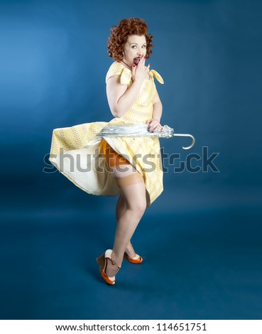Cute pinup girl holding an umbrella pulling up her dress - stock photo