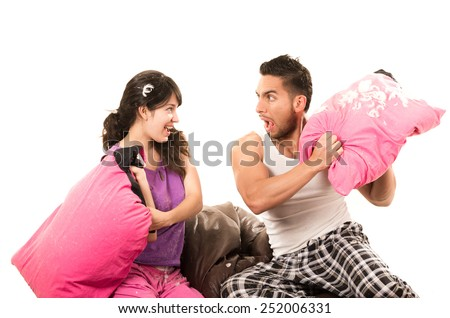 cute playful couple having a pillow fight isolated on white - stock photo