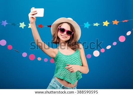 Cute playful little girl in hat and sunglasses taking selfie with mobile phone over blue background - stock photo