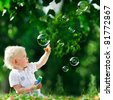 cute playful smiled blond one-and-half years old boy sitting on green grass outdoor playing with soap bubbles - stock photo
