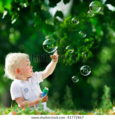 cute playful smiled blond one-and-half years old boy sitting on green grass outdoor playing with soap bubbles
