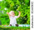 cute playful smiled blond 1.5 years old boy sitting on green grass outdor playing with soap bubbles - stock photo