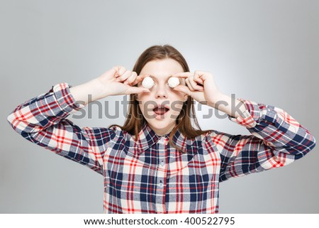 Cute playful teenage girl in plaid shirt covered her eyes with round white candies  - stock photo