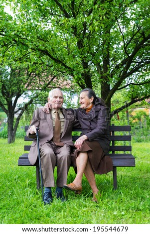 Cute 80 plus year old married couple posing for a portrait in their garden. Love forever concept.