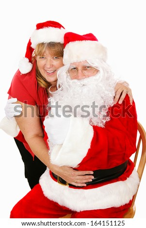 Cute portrait of Santa Clause getting a hug from his wife.  Isolated on white.   - stock photo