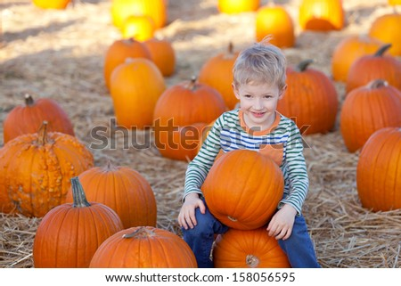 cute positive boy having fun at the pumpkin patch