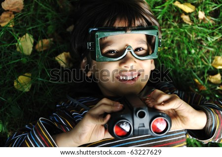 Cute positive boy with glasses and binoculars laying on ground and smiling - stock photo