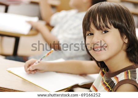 Cute positive boy writing and smiling. Indoor, school, classroom. - stock photo
