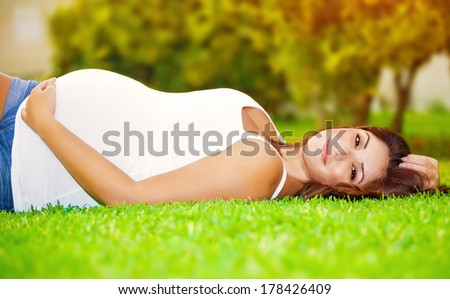 Cute pregnant woman lying down on fresh green grass on the backyard, happy parenthood, healthy pregnancy, spring season - stock photo