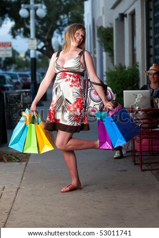 Cute pregnant woman shopping with colorful bags - stock photo