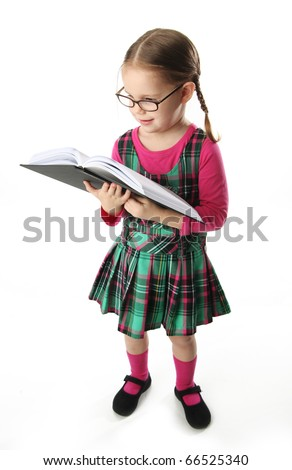 Cute preschool age girl wearing eyeglasses reading a book - stock photo