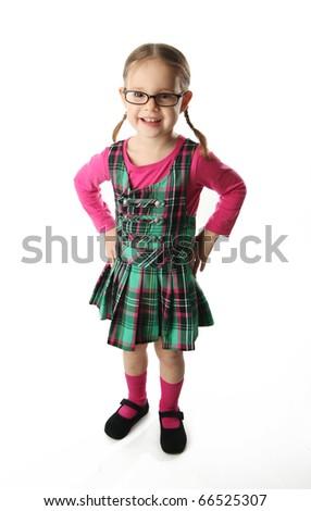 Cute preschool age girl wearing glasses and a plaid schoolgirl dress - stock photo