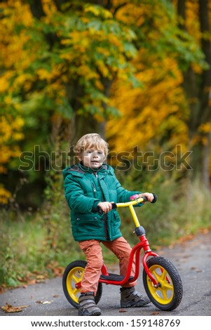 Cute preschool boy of three years riding bike in autumn forest. - stock photo