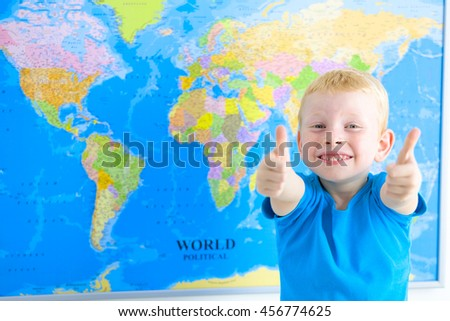 Cute preschool boy with world map - stock photo