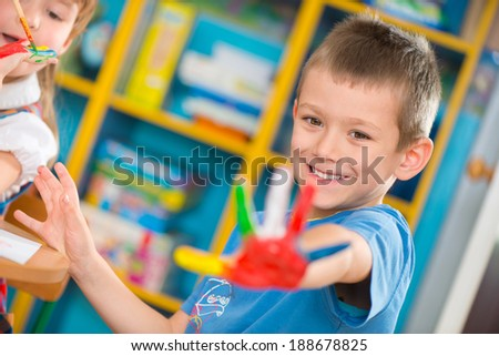 Cute preschool children painting with their palms at kindergarten - stock photo