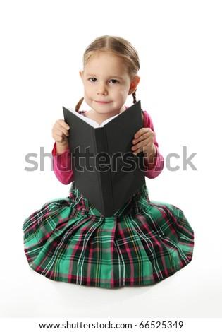 Cute preschool girl in a plaid dress kneeling reading a book - stock photo