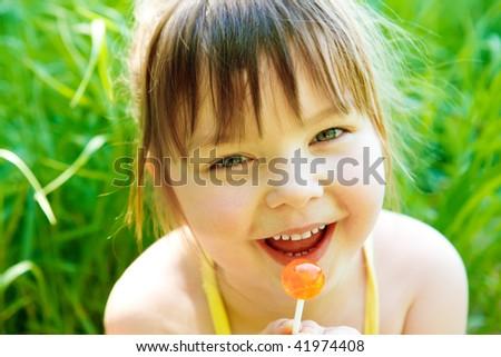 Cute preschool girl with lollipop, in park - stock photo