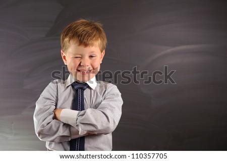 Cute preschooler against dark blackboard in classroom - stock photo