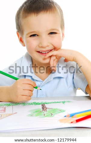 Cute preschooler boy draw using the green crayon - stock photo