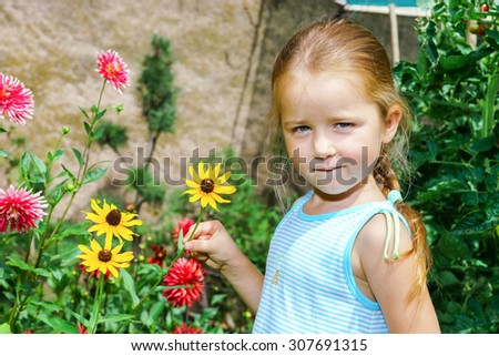 Cute preschooler girl portrait with natural flowers in the garden - stock photo